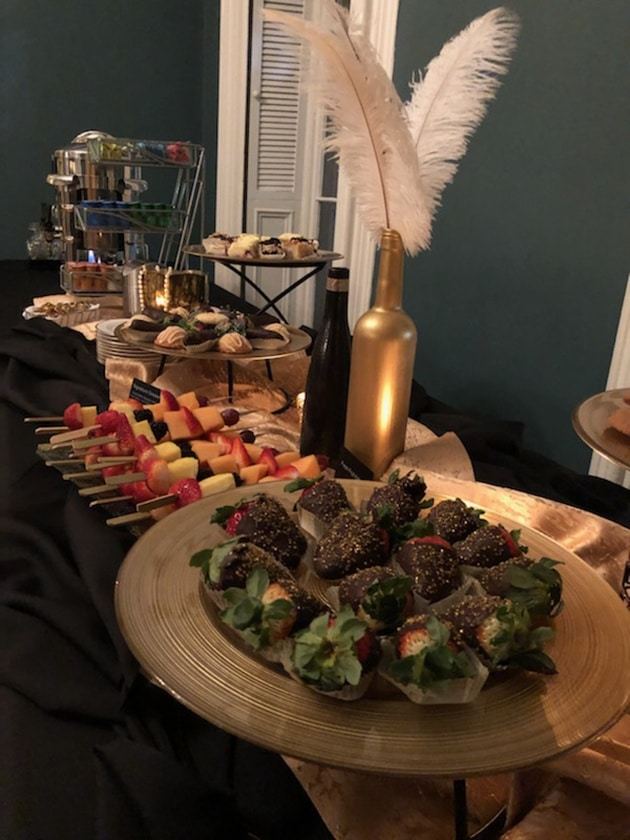 Chocolate covered strawberries and fruit kabobs on a dessert table