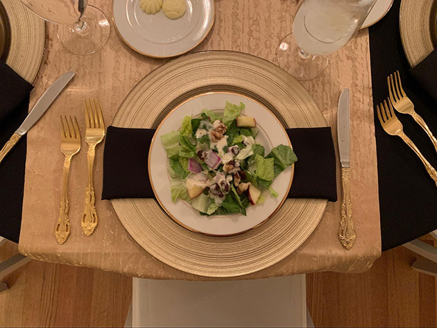 Plated Waldorf salad on a gold plate with gold tableware