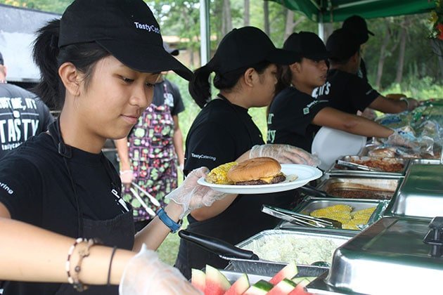 Staff Place Food on Plates for Guests