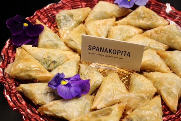 Spanakopita appetizer on a red serving dish