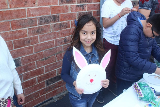 Adorable young girl posing with an Easter bunny face she made at a company party