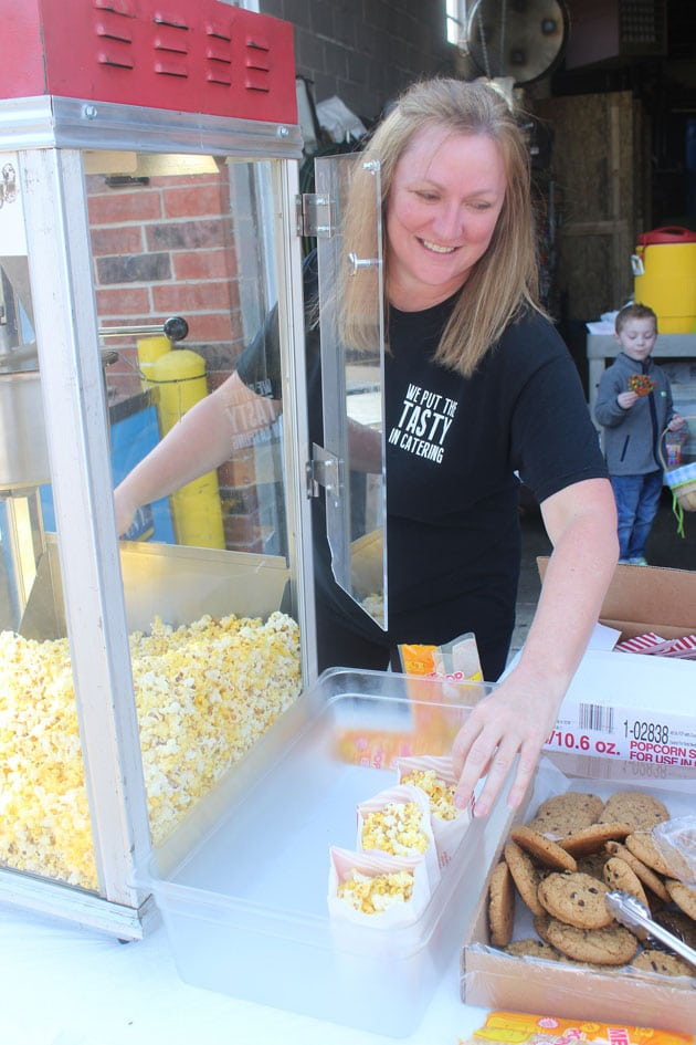 Woman scooping popcorn into bags for a snack table at a company party