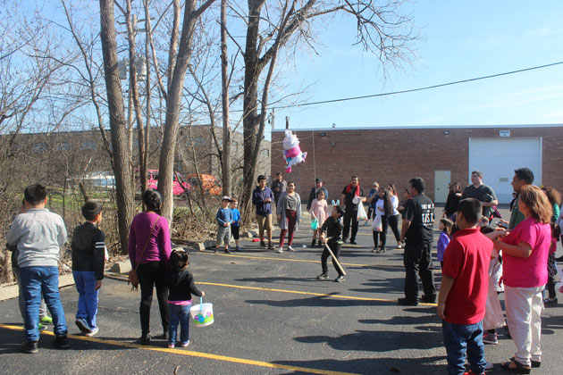 Young boy hitting Easter bunny pinata surrounded by family and friends at company party