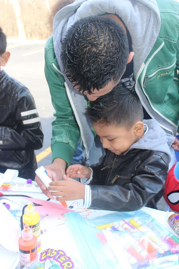 Happy young boy doing Easter arts and crafts with his dad.