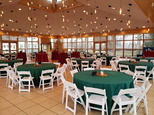 Tables and chairs set for an event with holiday lights