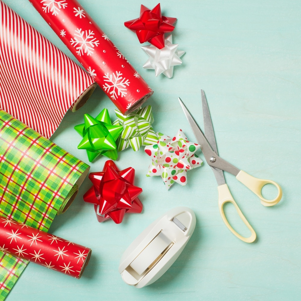 Holiday wrapping paper, bows, scissors and tape