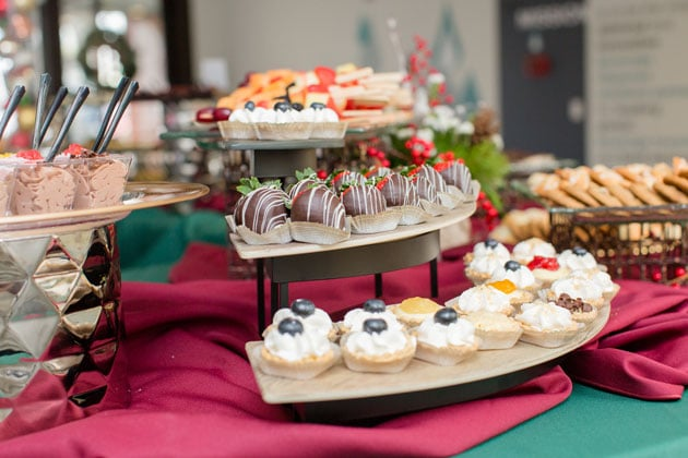 Dessert table featuring chocolate covered strawberries and mini pies