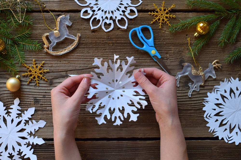 Hands holding a paper snowflake with scissors and materials in the background