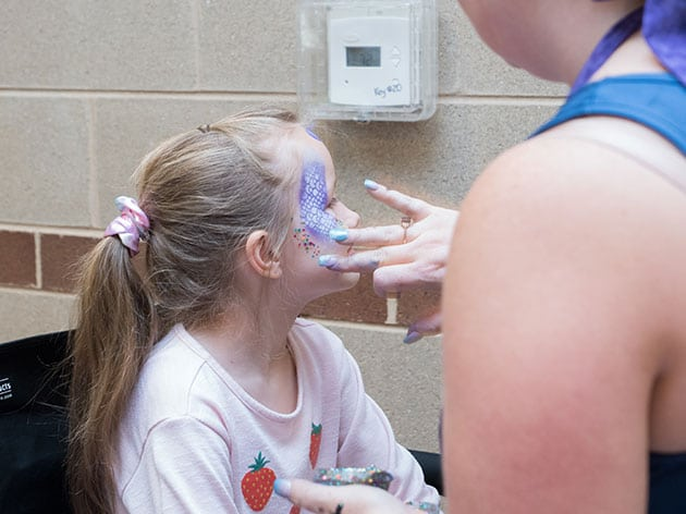Young girl having her face painted