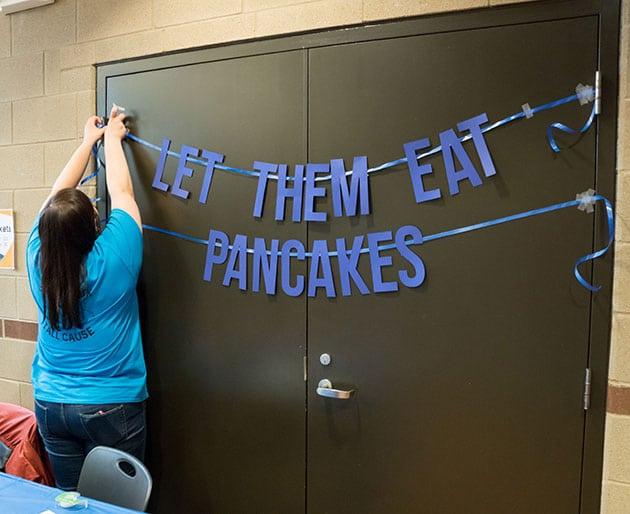 Woman hanging banner that says Let Them Eat Pancakes