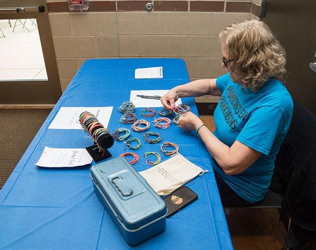 Volunteer arranging bracelets for sale on a table