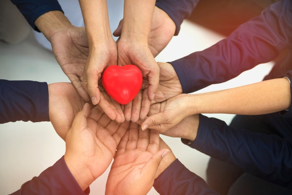 multiple hands coming together to hold a heart