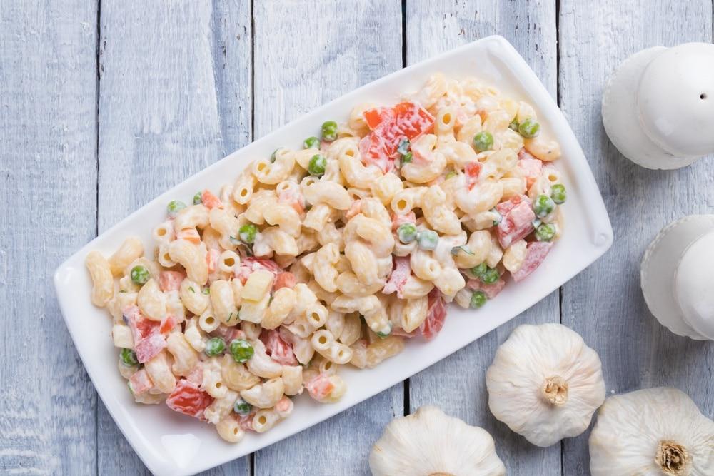 Macaroni salad on a white rectangular serving platter