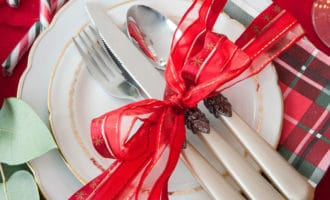 Knife, fork and spoon on a white plate tied with a red bow on a flannel placemat
