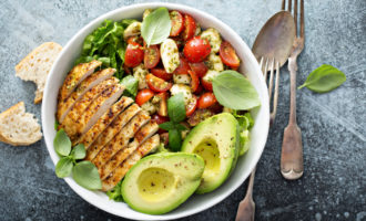 Healthy salad with grilled chicken, avocado and tomatoes