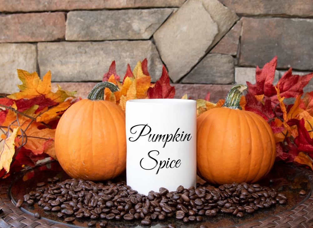 Coffee cup with pumpkin spice written on it on a table with pumpkins and fall leaves