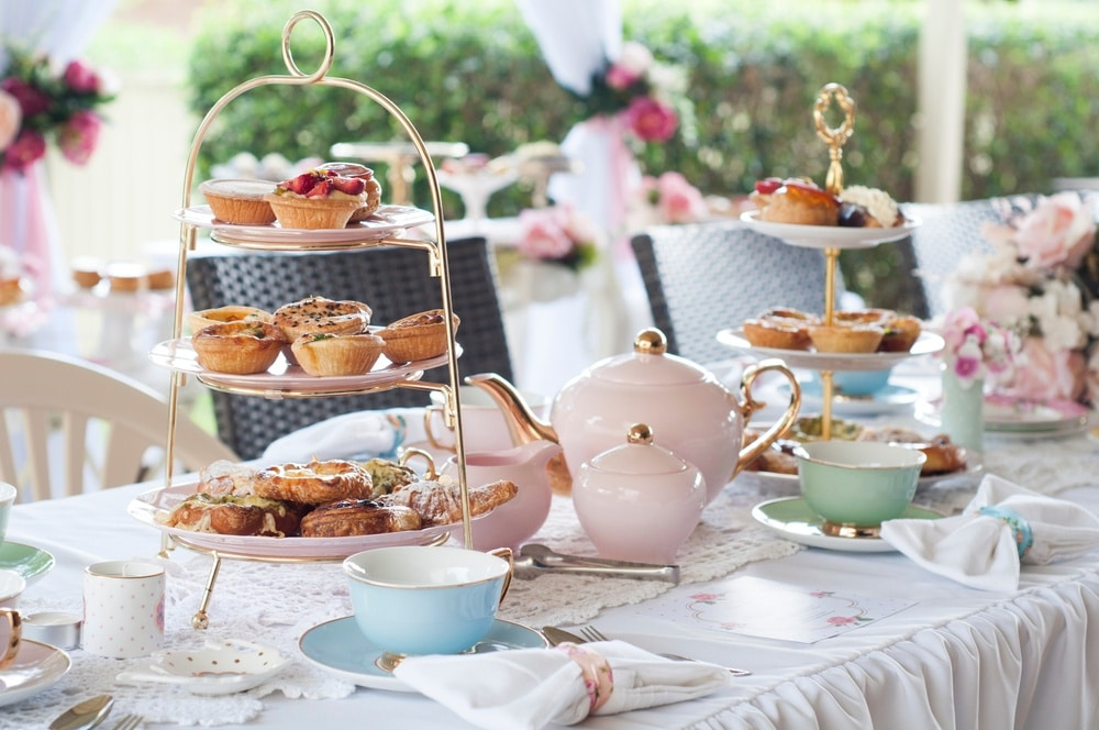 Table with white tablecloth set with pastries and pastel plateware