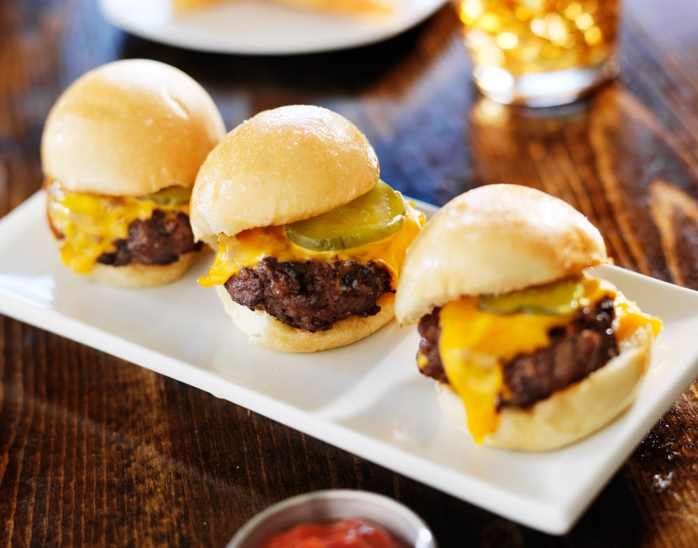 Three cheeseburger sliders on a white serving platter