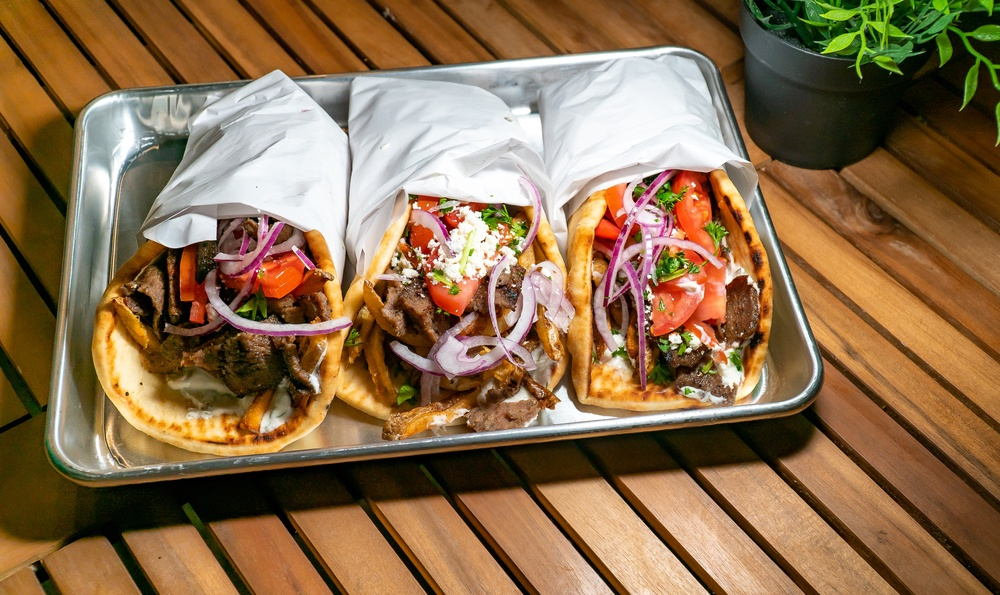 Greek gyros wrapped in foil on a tray on a wooden table