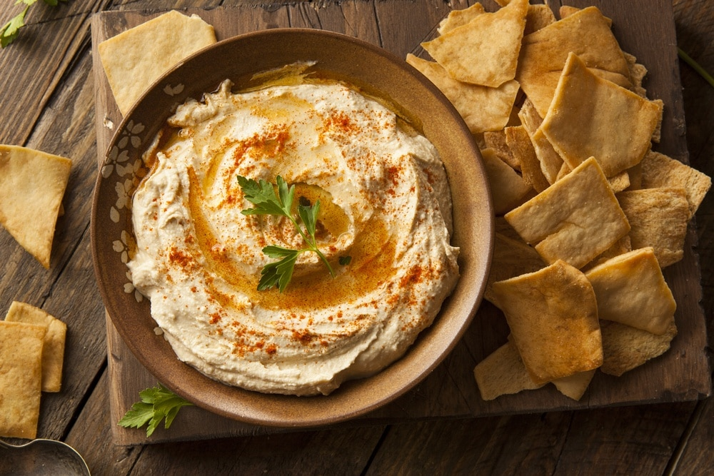 Bowl of hummus with pita chips on the side on a wooden cutting board