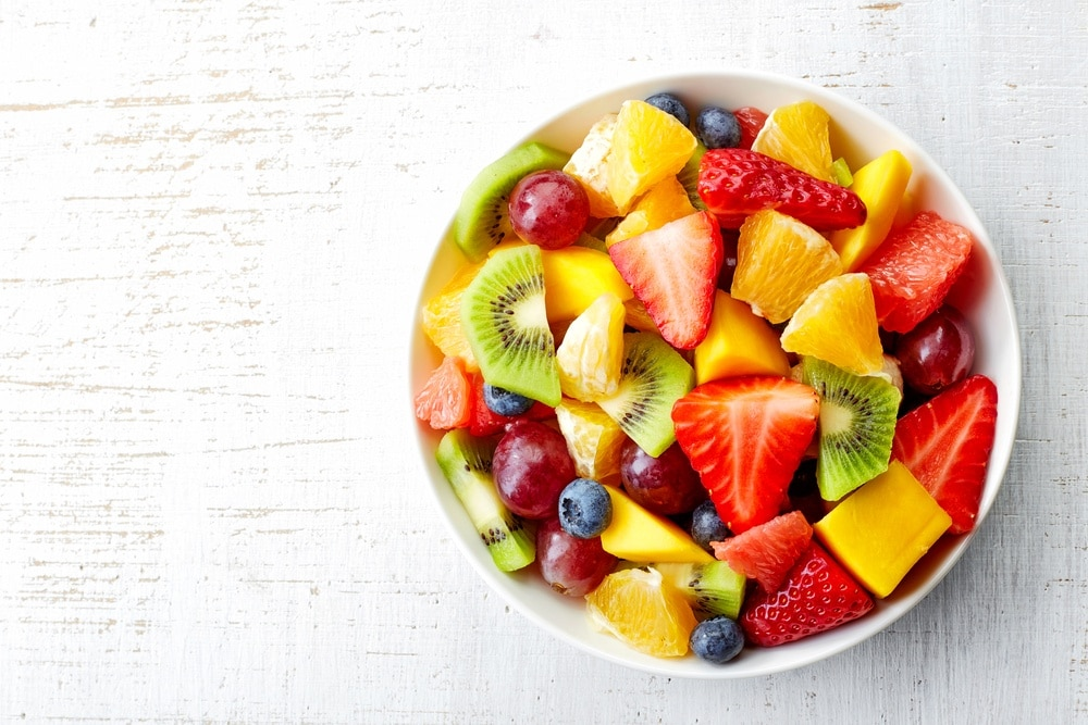 Bowl of fresh fruit on a lite gray background