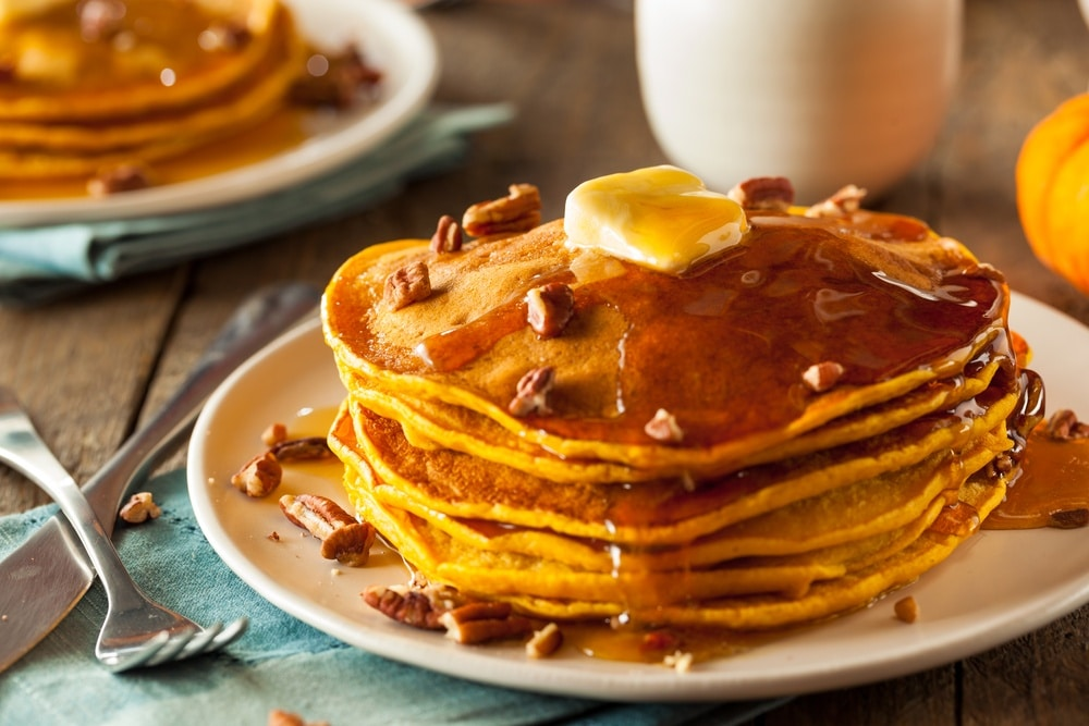 Pumpkin pancakes stacked on a plate with butter and syrup on top