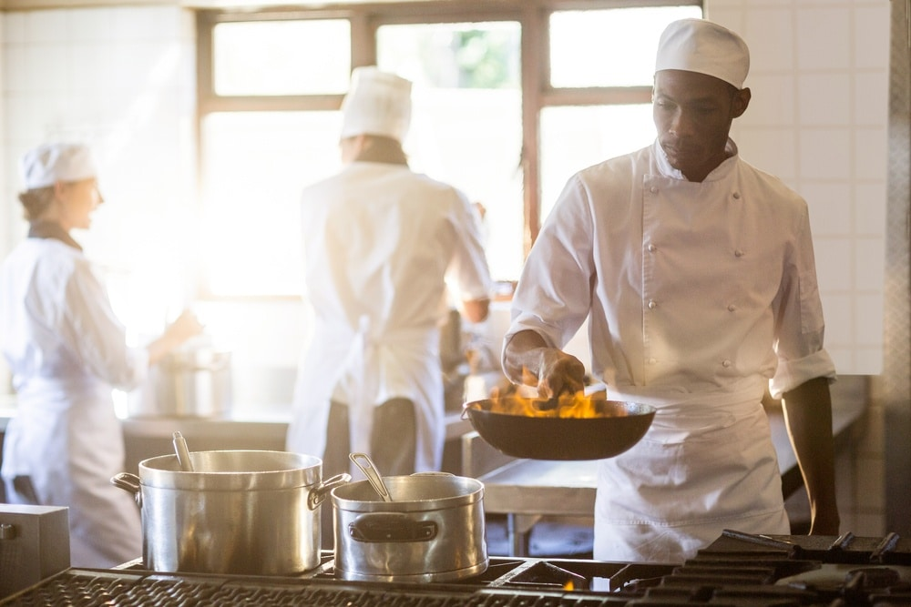 Chefs in stainless steel commercial kitchen