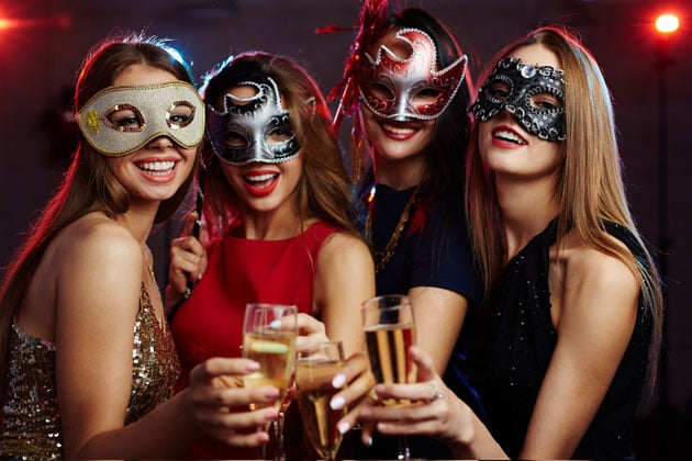 Attractive women in masquerade masks with champagne flutes