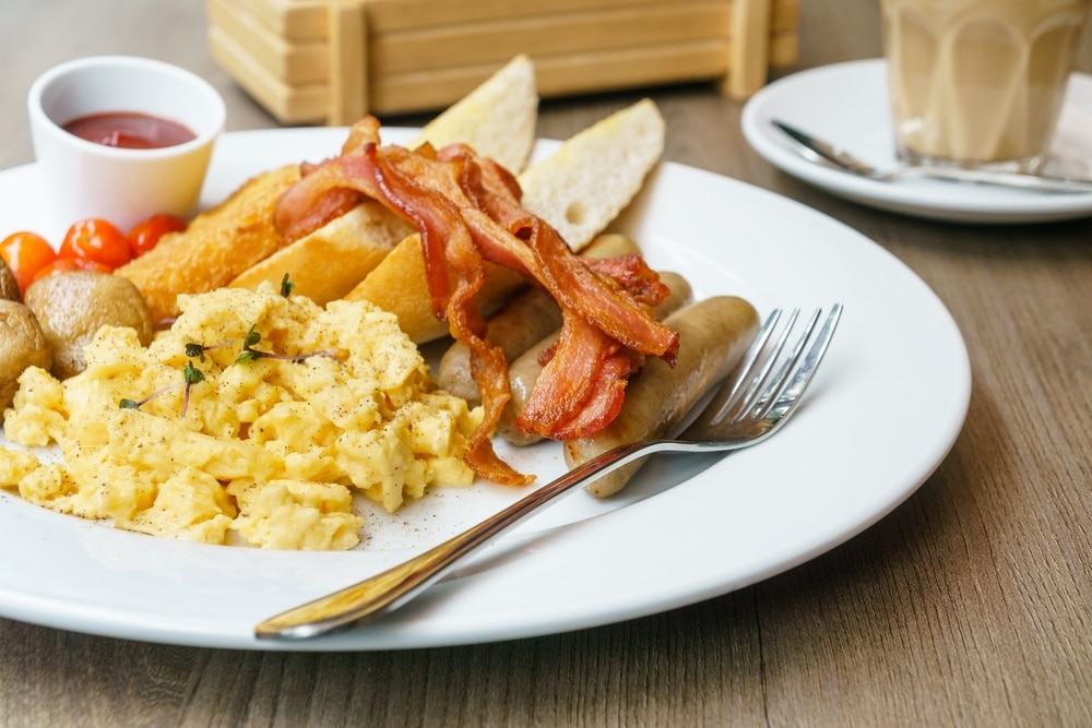 Eggs, Potatoes, Bacon, Sausage and bread on a breakfast plate