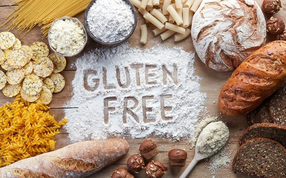 Gluten Free written in flour on a cutting board surrounded by gluten food