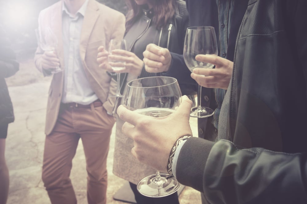 Business people standing around with cocktail glasses in their hands