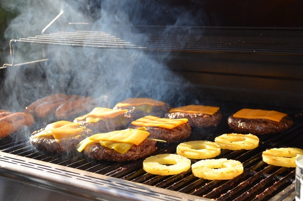Hotdogs, cheese burgers and pineapple slices on the grill